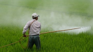 farmer applying pesticides to field