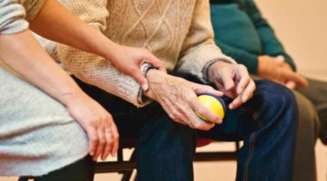 Elder man in nursing home holding a ball
