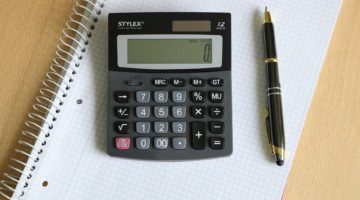 A calculator and pen on a notepad