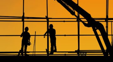 construction workers at twilight with crane in background