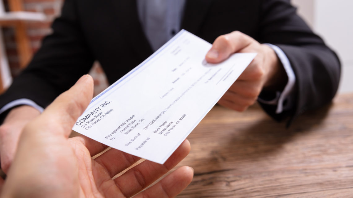 Man's Hands Giving Check To Other Person