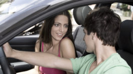 A teenage girl and teenage boy sitting in a car