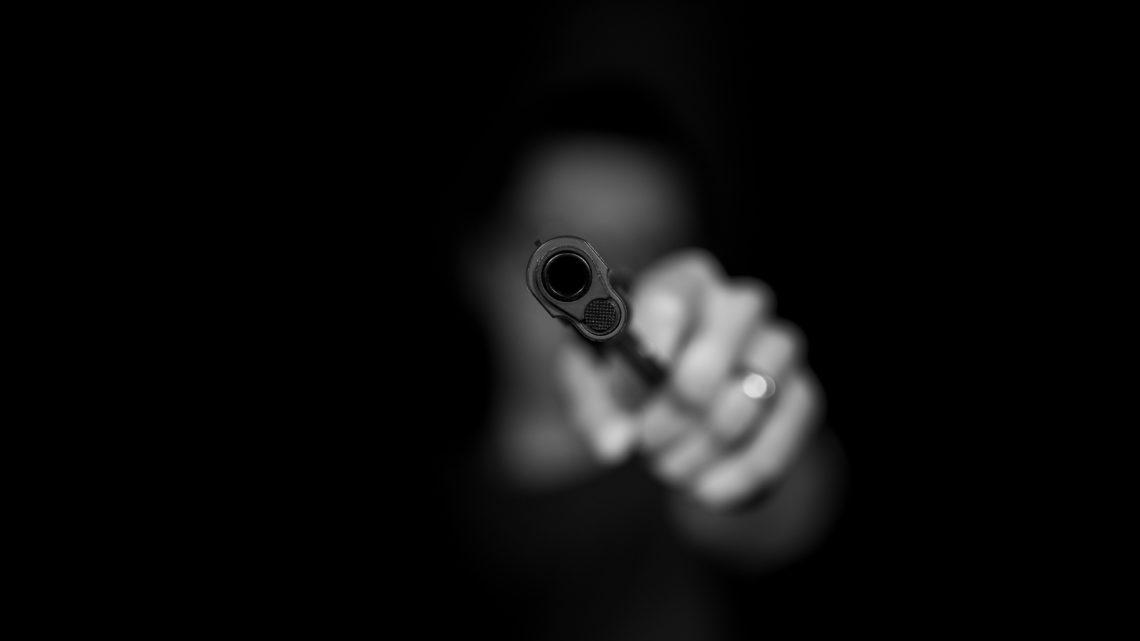 person pointing handgun at camera