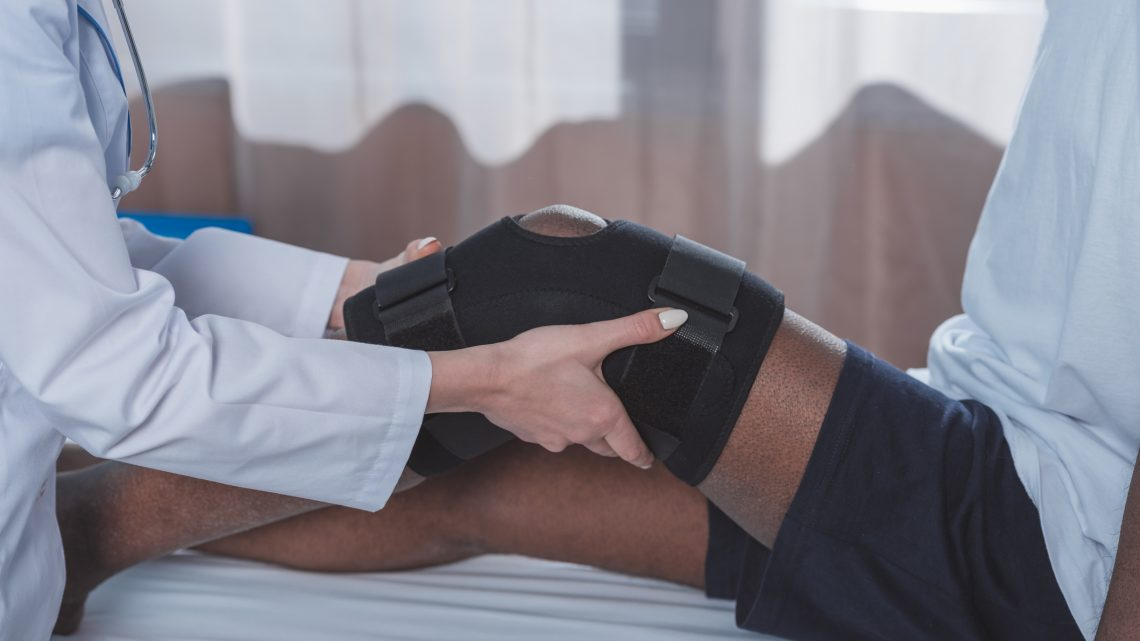 Cropped image of doctor putting knee brace on patient