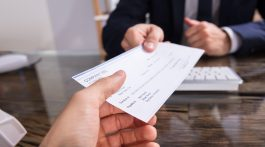 detail shot of one person handing a check to another person